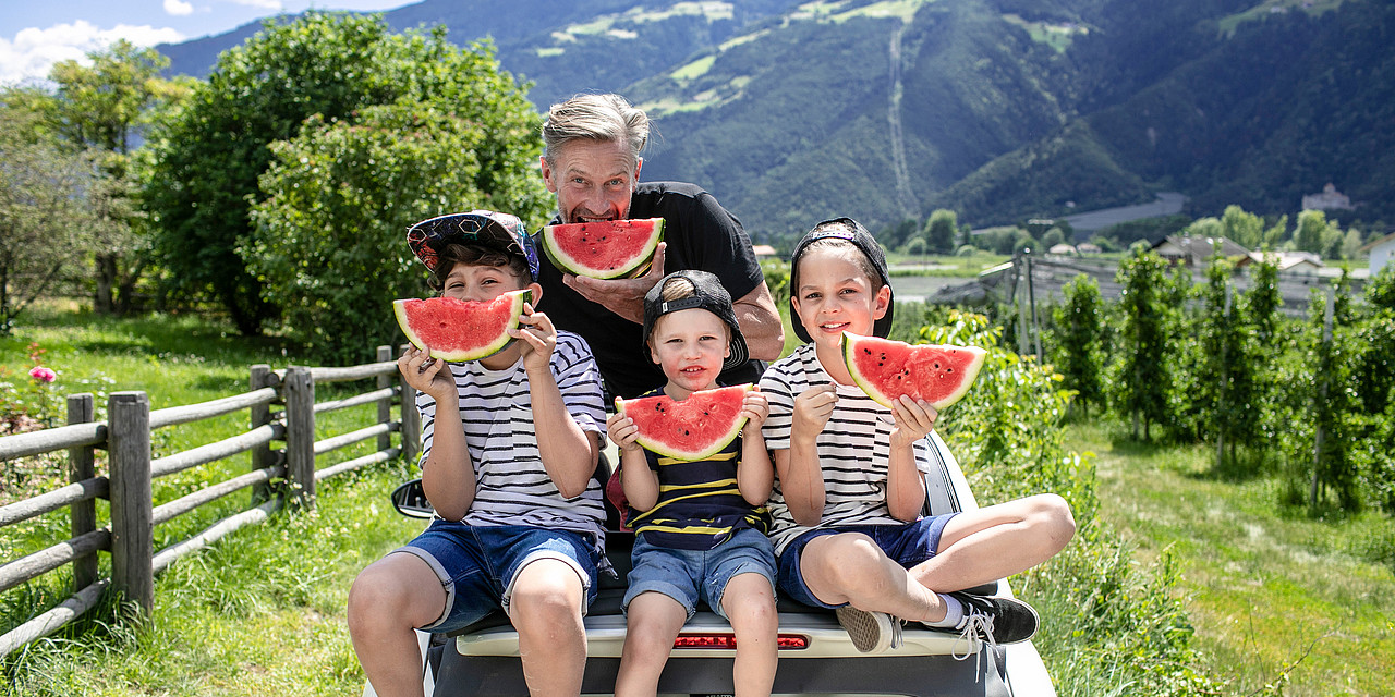 Man and three children eating a water melon outdoors in the family hotel Sonnen Resort
