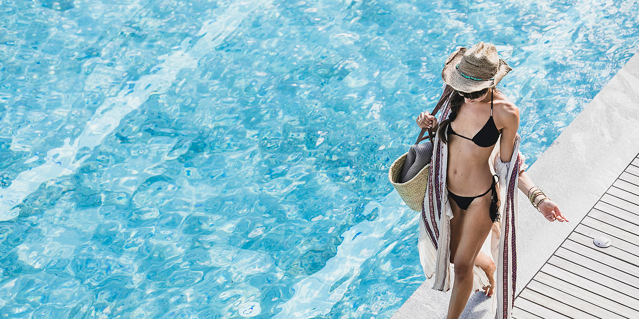 Woman walking at the pool in the wellness hotel Sonnen Resort in South Tyrol